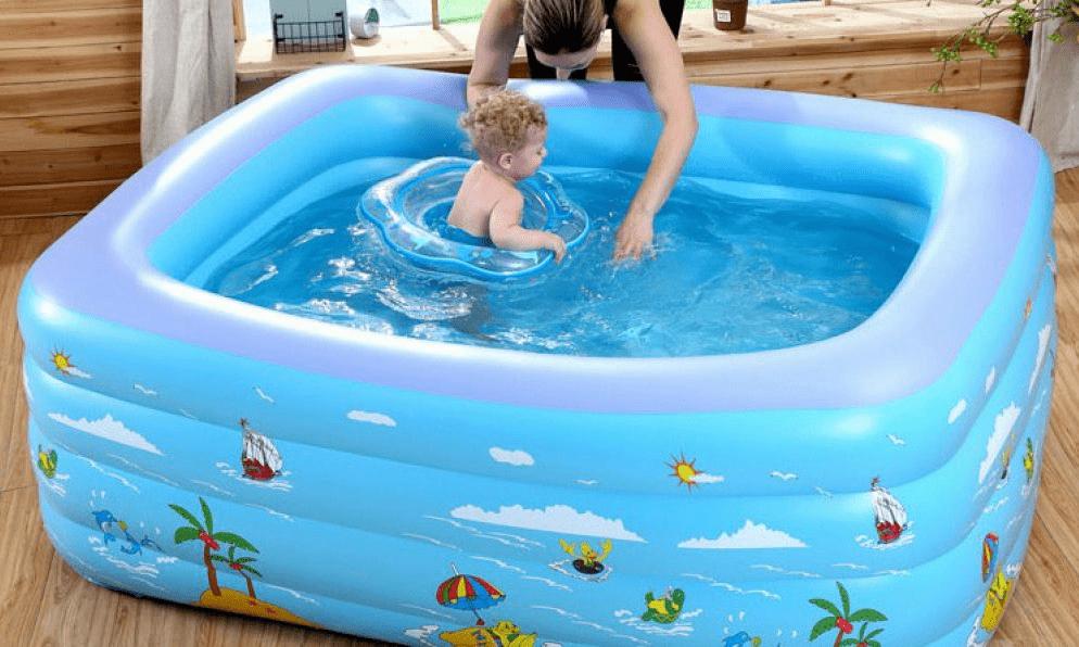 mẹ đang giúp bé vào bể bơi